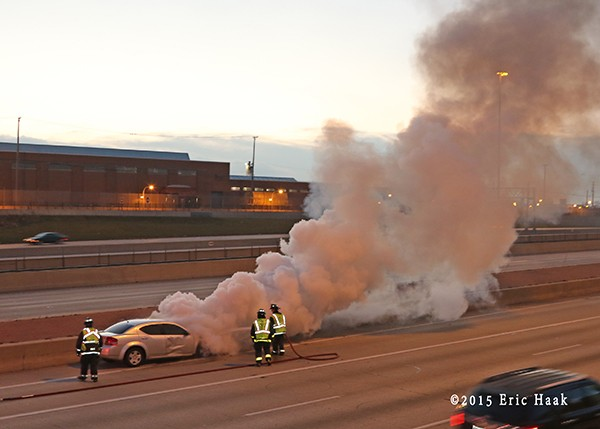 firemen extinguish a car fire on the expressway