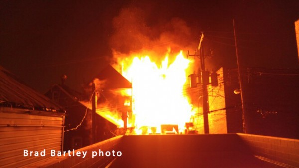 fire engulfs an alley garage