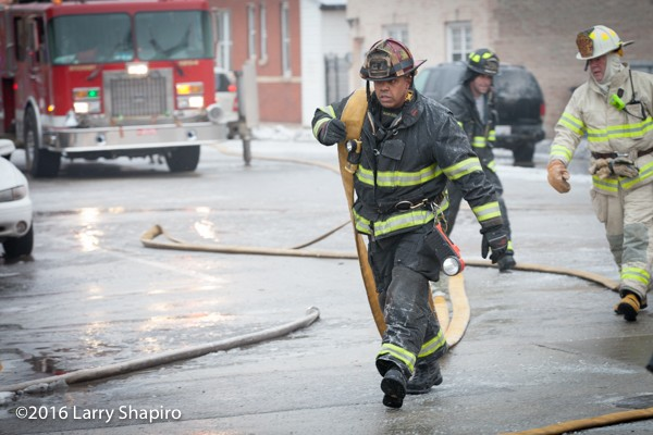 African American firefighter pulls hose at fire scene