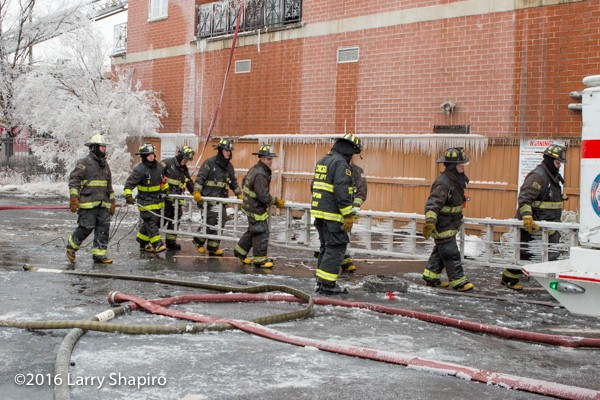 firemen carry frozen ladder covered with ice