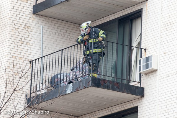 fireman on balcony with shielding resident from fire