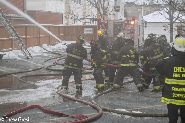 firefighters handle hose line at fire scene