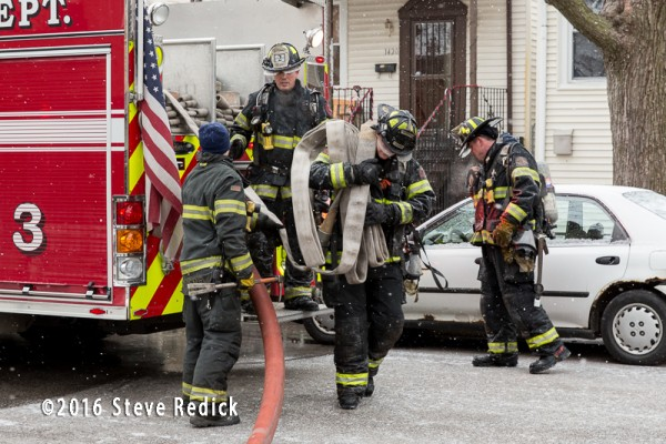 firemen grab hose off engine
