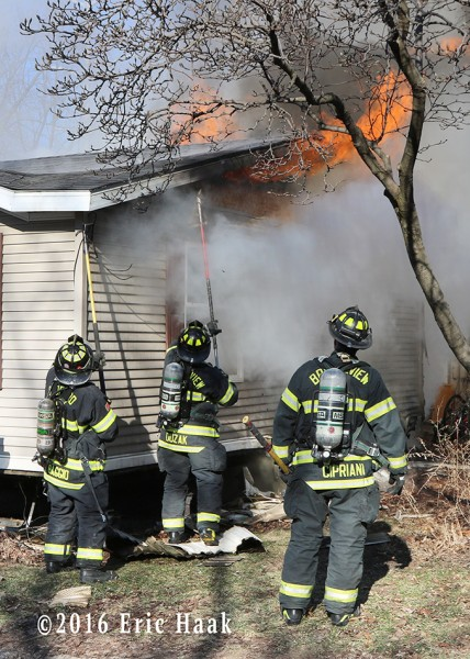 firefighters battle fire in a mobile home