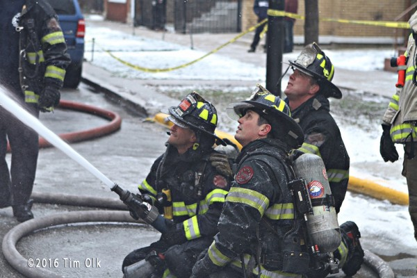 firefighters with hose at fire scene