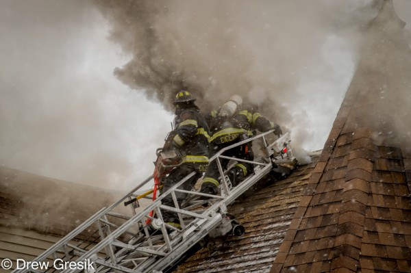 firemen cent roof at fire with heavy smoke
