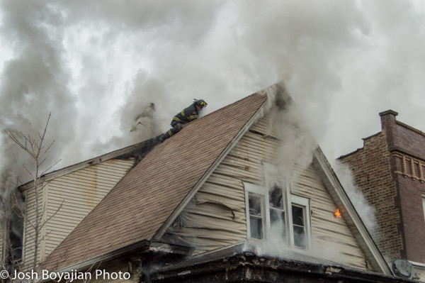 firemen on peaked roof during fire
