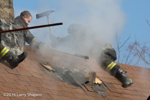 firefighters vent peaked roof with axe