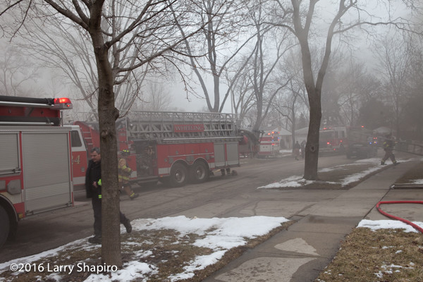 fire trucks on street with smoke from fire