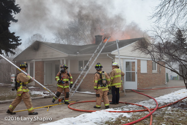 firefighters outside house on fire