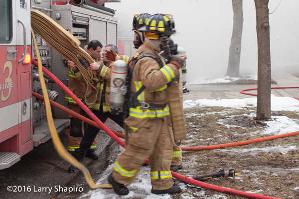 firemen pull hose at fire