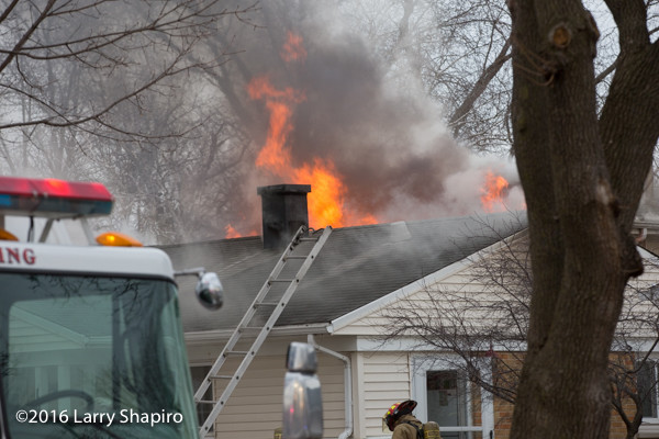 flames and smoke through roof of house