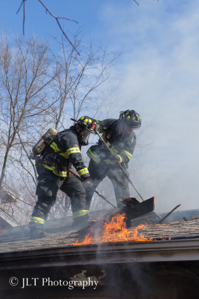 firemen on roof during house fire