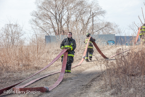 Firemen drag hose at fire scene