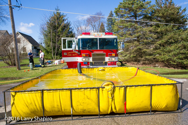 Pierce fire engine at fire scene drafting from portable tank