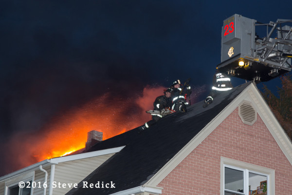 firemen on peak roof with fire at night