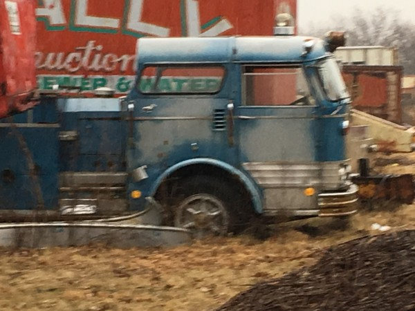 unidentified blue C Model Mack fire engine rusting in a field