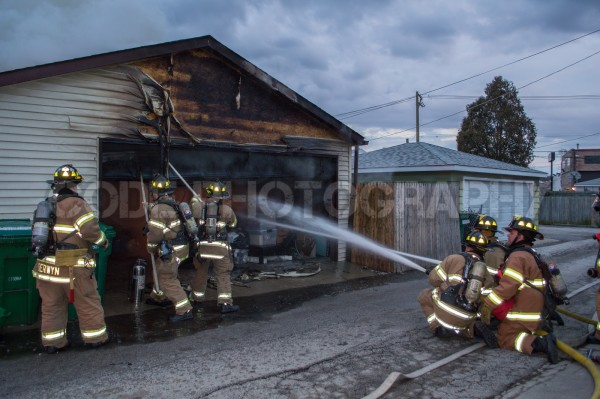 firemen battle alley garage fire