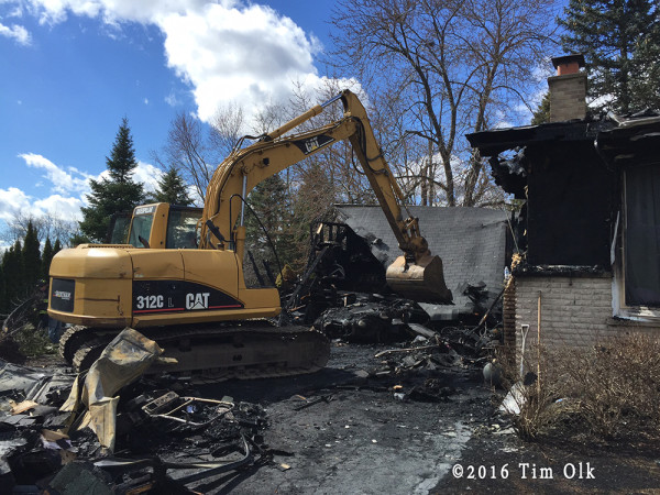excavator clears debris from house fire