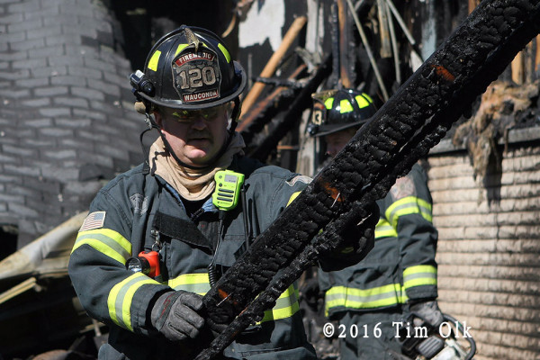 firefighter overhauls after garage fire