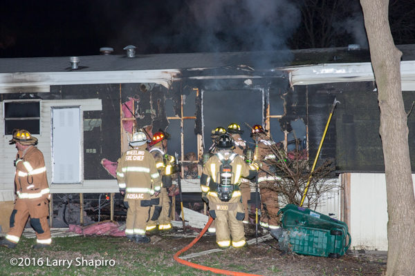 firefighters battle a mobile home fire