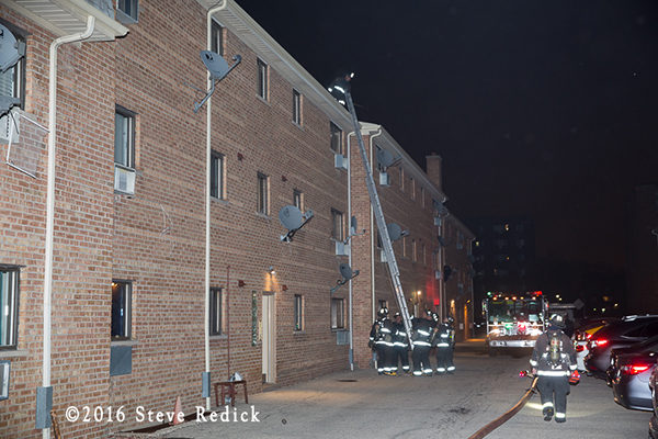 firefighters with ground ladder to roof of apartment building