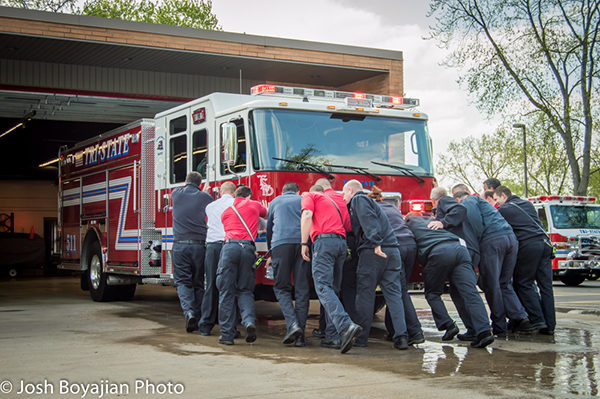 firefighters push new fire engine into station after wetdown
