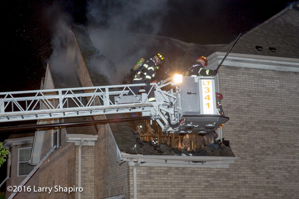firemen work off tower ladder platform at fire