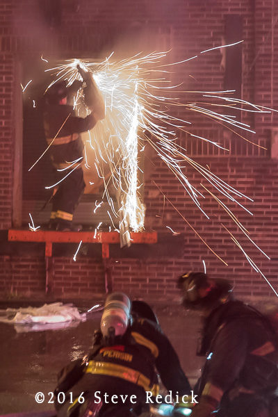 firefighter cuts metal door at night