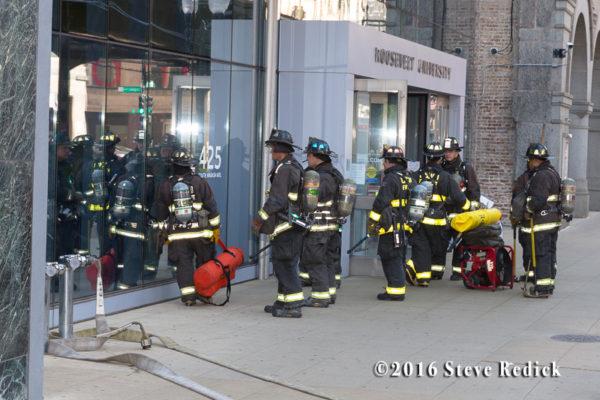 firemen carry high-rise hose packs