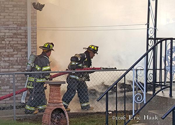 firemen advance hose line on fire