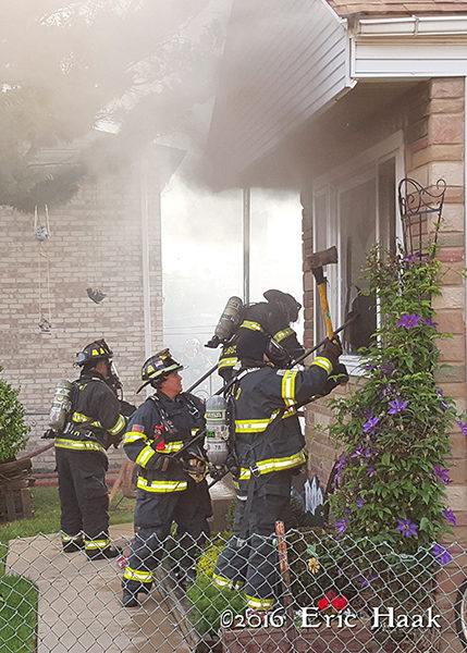 firemen break windows to vent house on fire