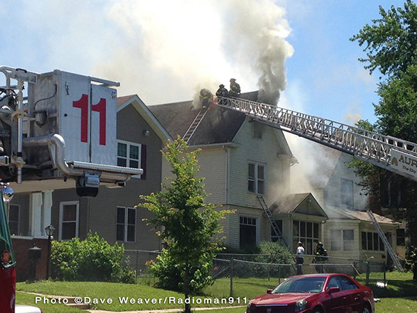 firefighters climb aerial to roof