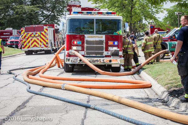 Pierce fire engine with lots of charged hose at fire scene