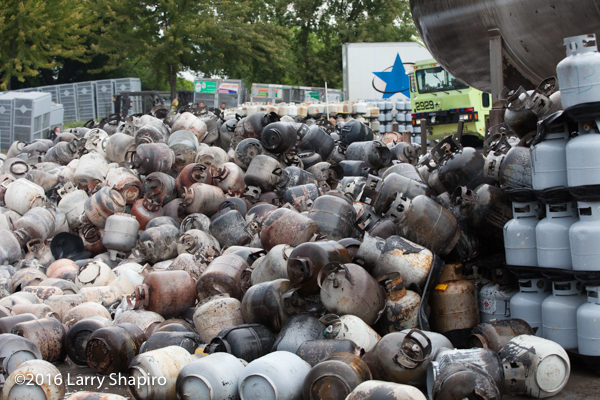 aftermath of fire at propane tank service company with charred propane tanks