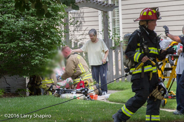 firefighter paramedic aids elderly fire victim