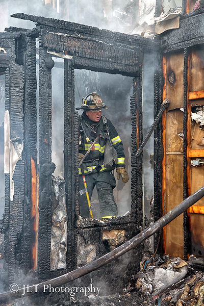 firefighter inspects house fire aftermath