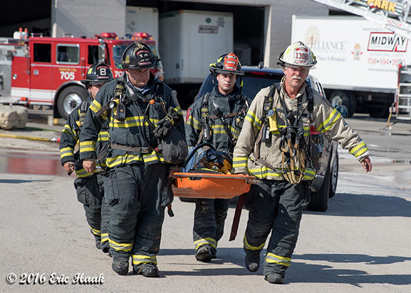 firefighters carry RIT equipment at fire scene