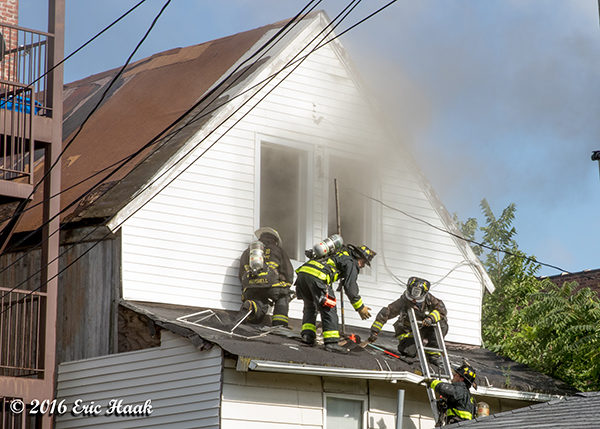 firefighters on roof of house with smoke