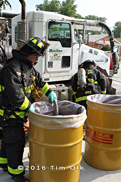 Chicago FD haz mat techs clean diesel fuel spill from ruptured saddle tank