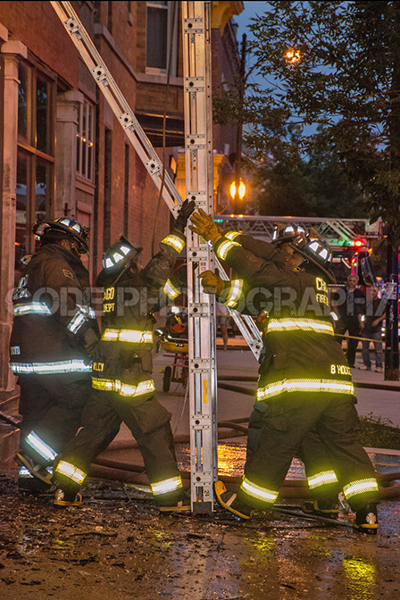 firefighters raise ground ladder at night