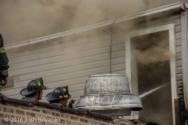 firefighters at work with hose line