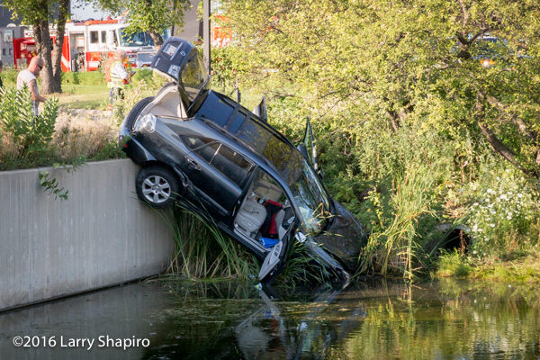 an SUV dangles over a retaining wall of a pond