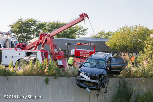 heavy wrecker picks up car from retention pond
