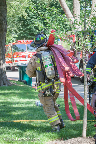 firefighter carries hose load over his shoulder
