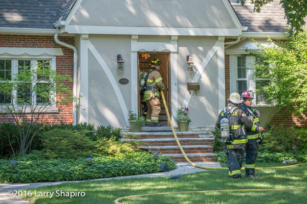 firefighter takes a line through the front door