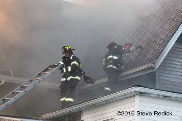 firefighters on roof with smoke