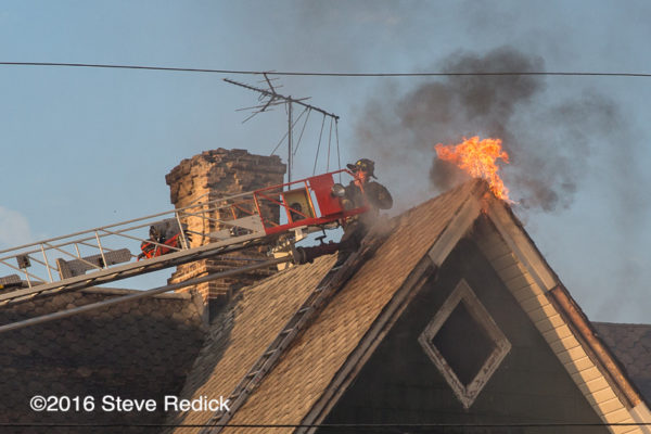 firefighters on aerial ladder with flames from the roof of a house