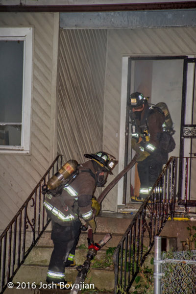 firefighters enter house with hose
