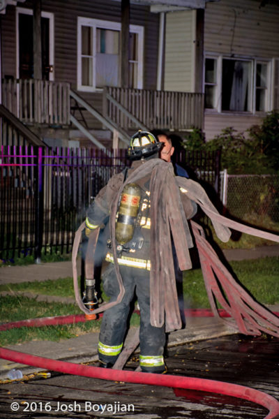 firefighter carries hose at fire scene